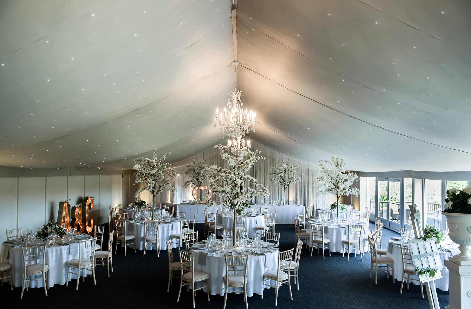 The Pavilion at Combermere Abbey is decorated with white blossom trees for an elegant wedding breakfast