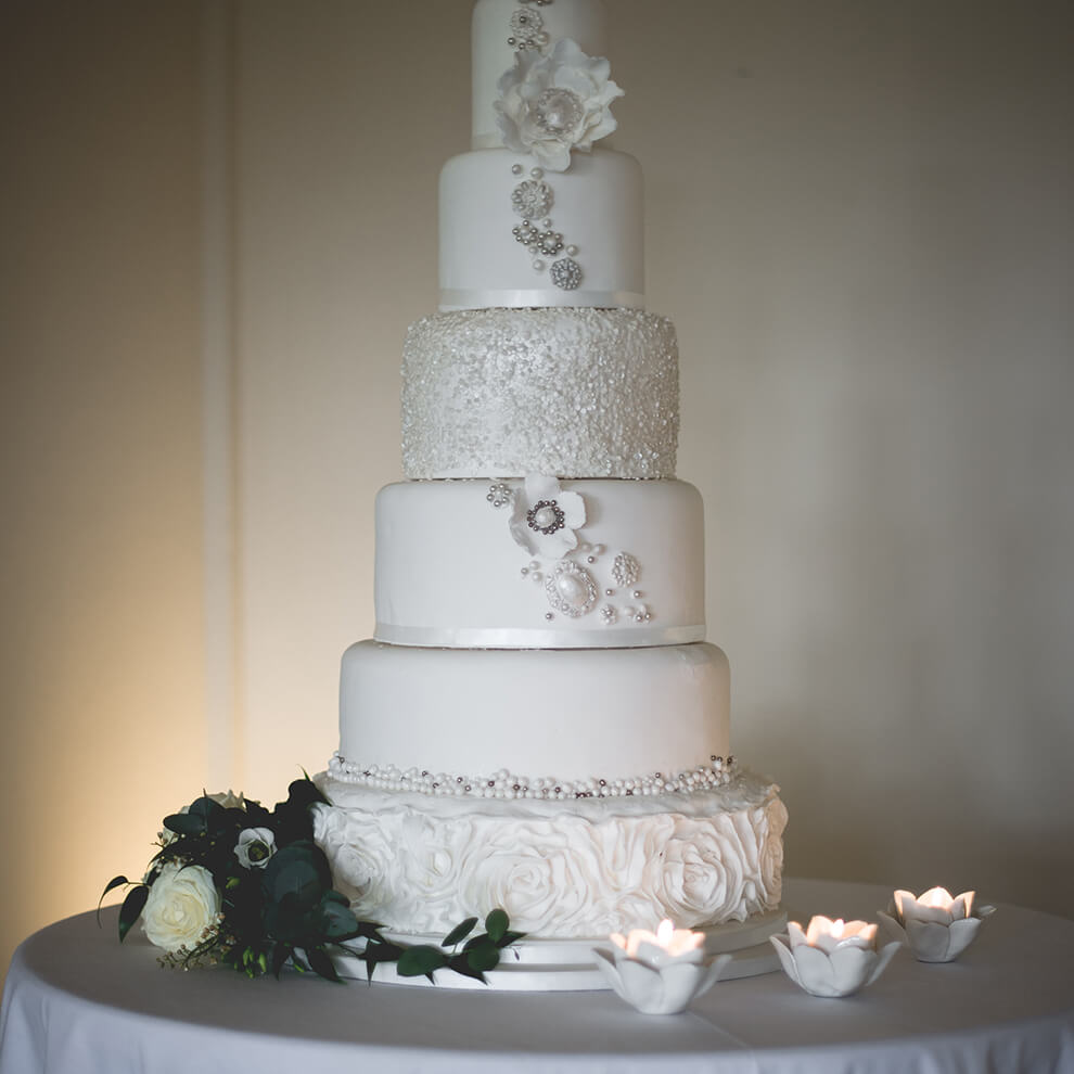 A six-tiered white wedding cake is decorated with beautiful details for a wedding at Combermere Abbey
