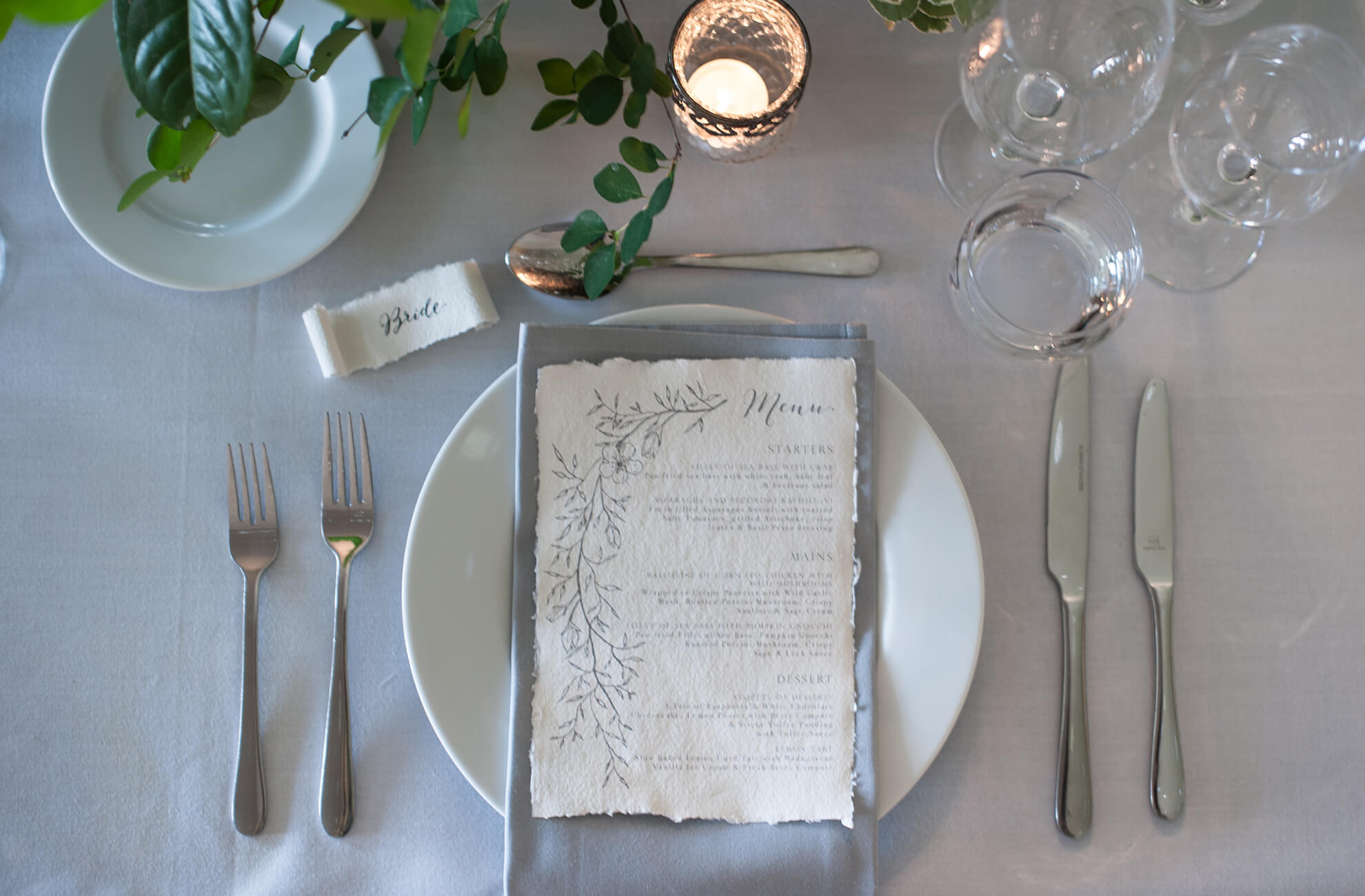 Calligraphy name cards and menus sit on top of grey serviettes for an elegant wedding table place setting at Combermere Abbey