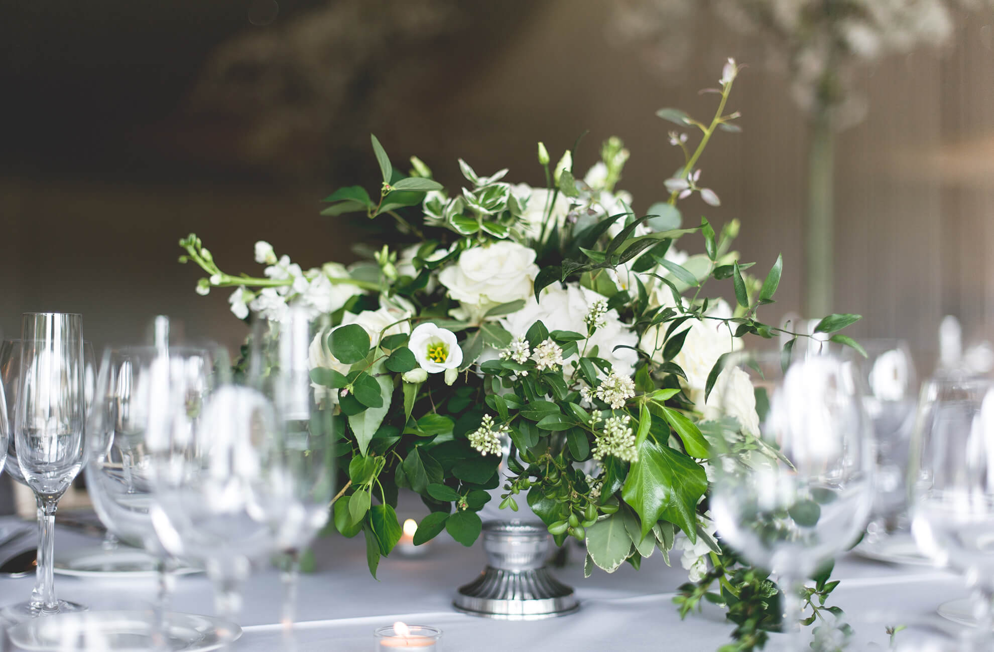 White and green wedding flowers sit in silver urns for stunning wedding table centrepieces at a Combermere Abbey wedding