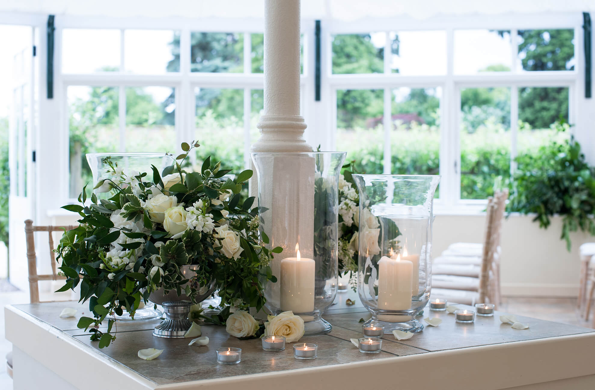 In the Glasshouse at this Cheshire wedding venue white wedding flowers and greenery are used as wedding decorations