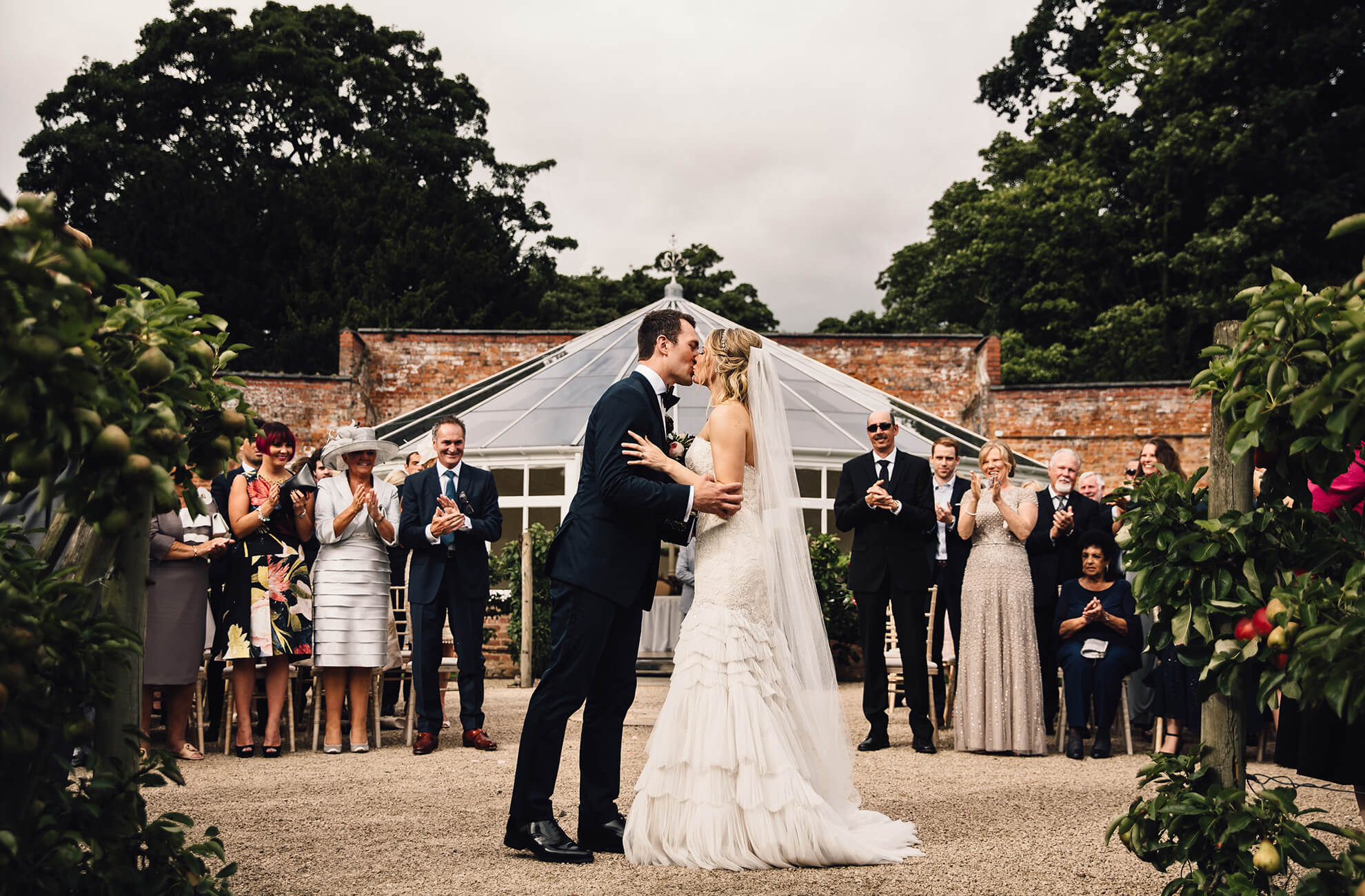 The bride and groom share a kiss in front of the Glasshouse at Combermere Abbey on their wedding day