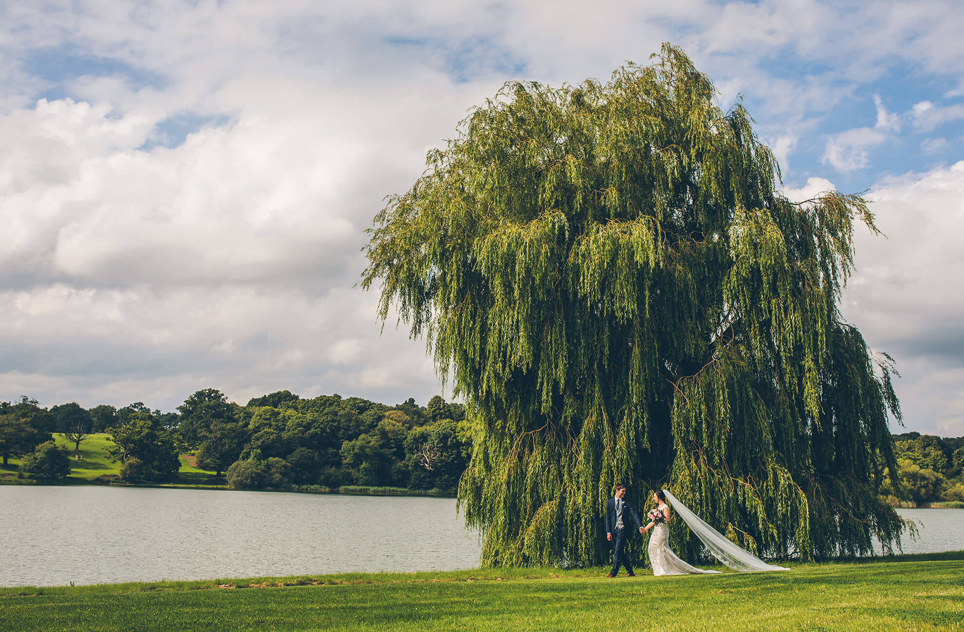 Newlyweds explore the grounds at this stunning lakeside wedding venue in Cheshire