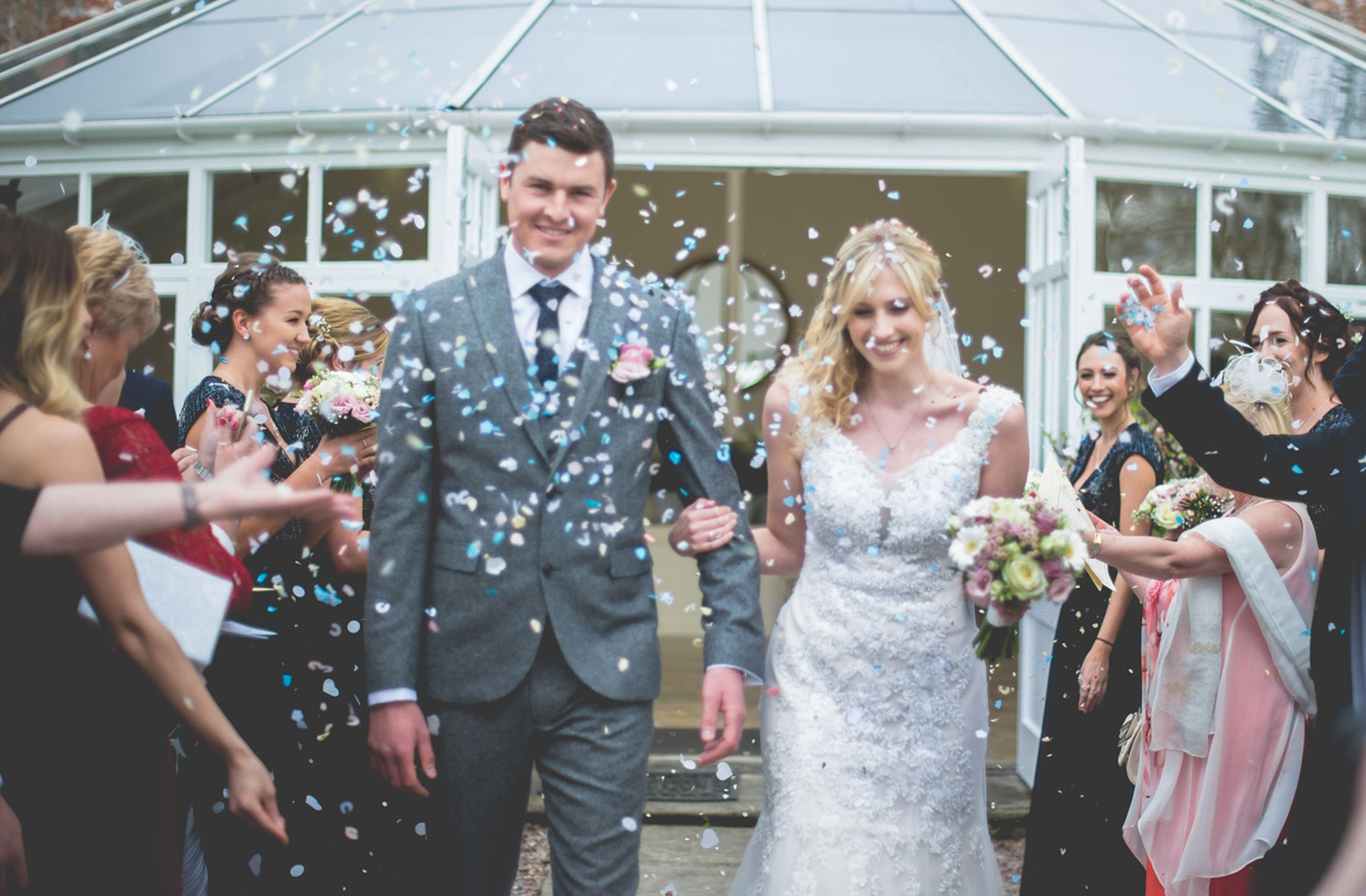 A bride and groom are showered in wedding confetti by guests after their wedding ceremony at Combermere Abbey