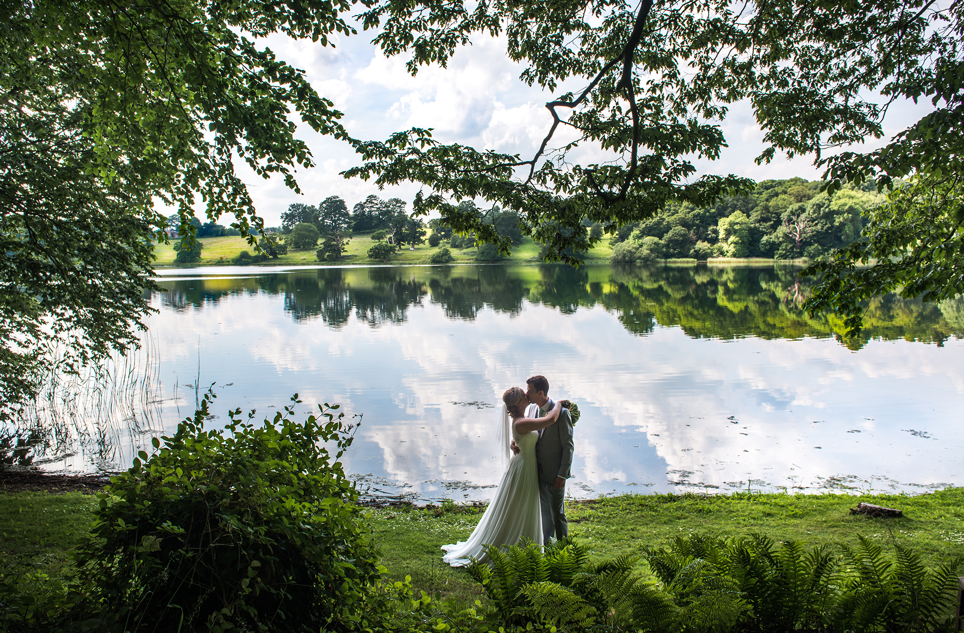 The bride and groom share a kiss by the mere at Combermere Abbey wedding venue in Cheshire
