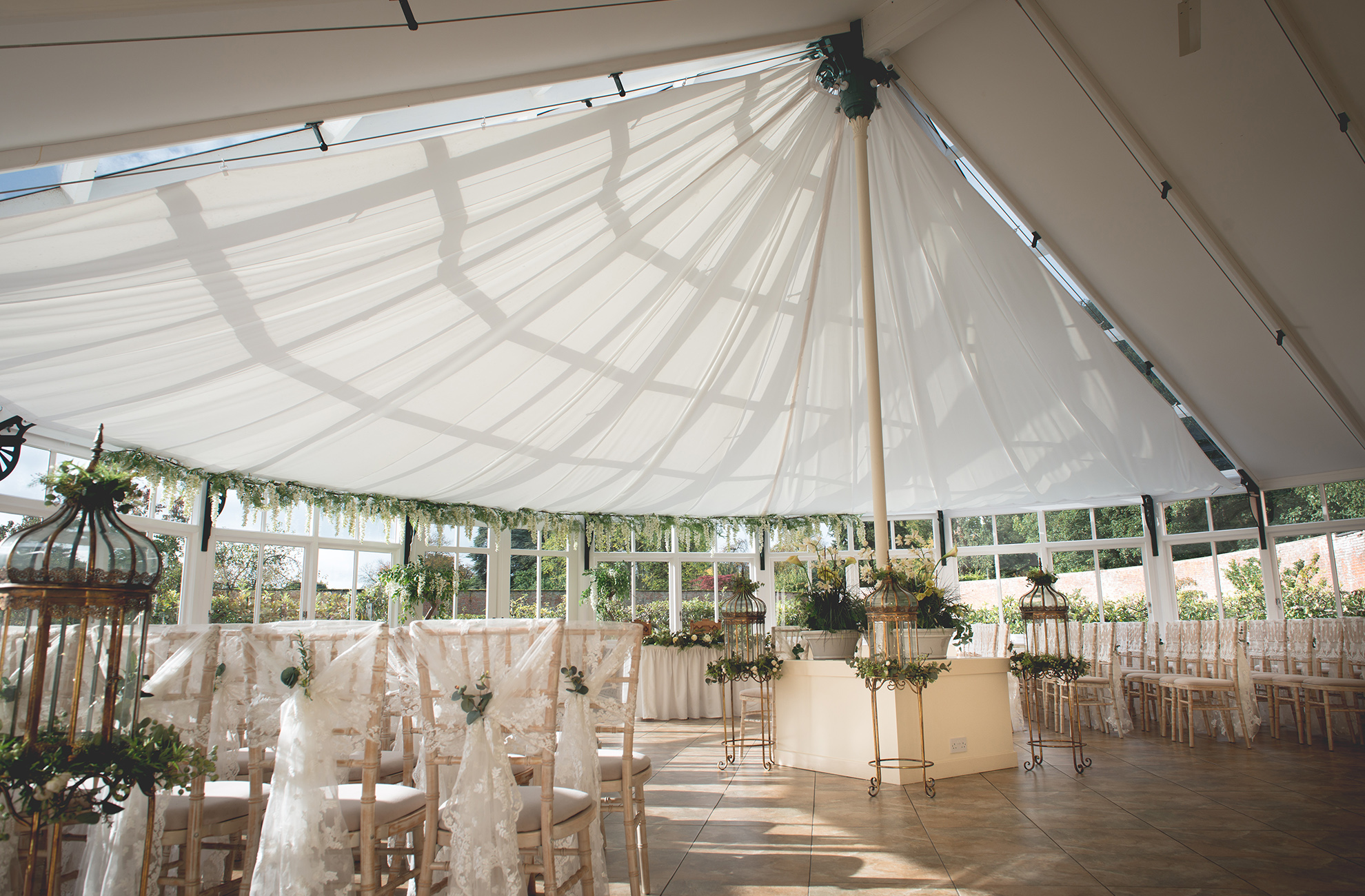 The glasshouse at Combermere Abbey wedding venue in Cheshire is set up for a beautiful wedding ceremony