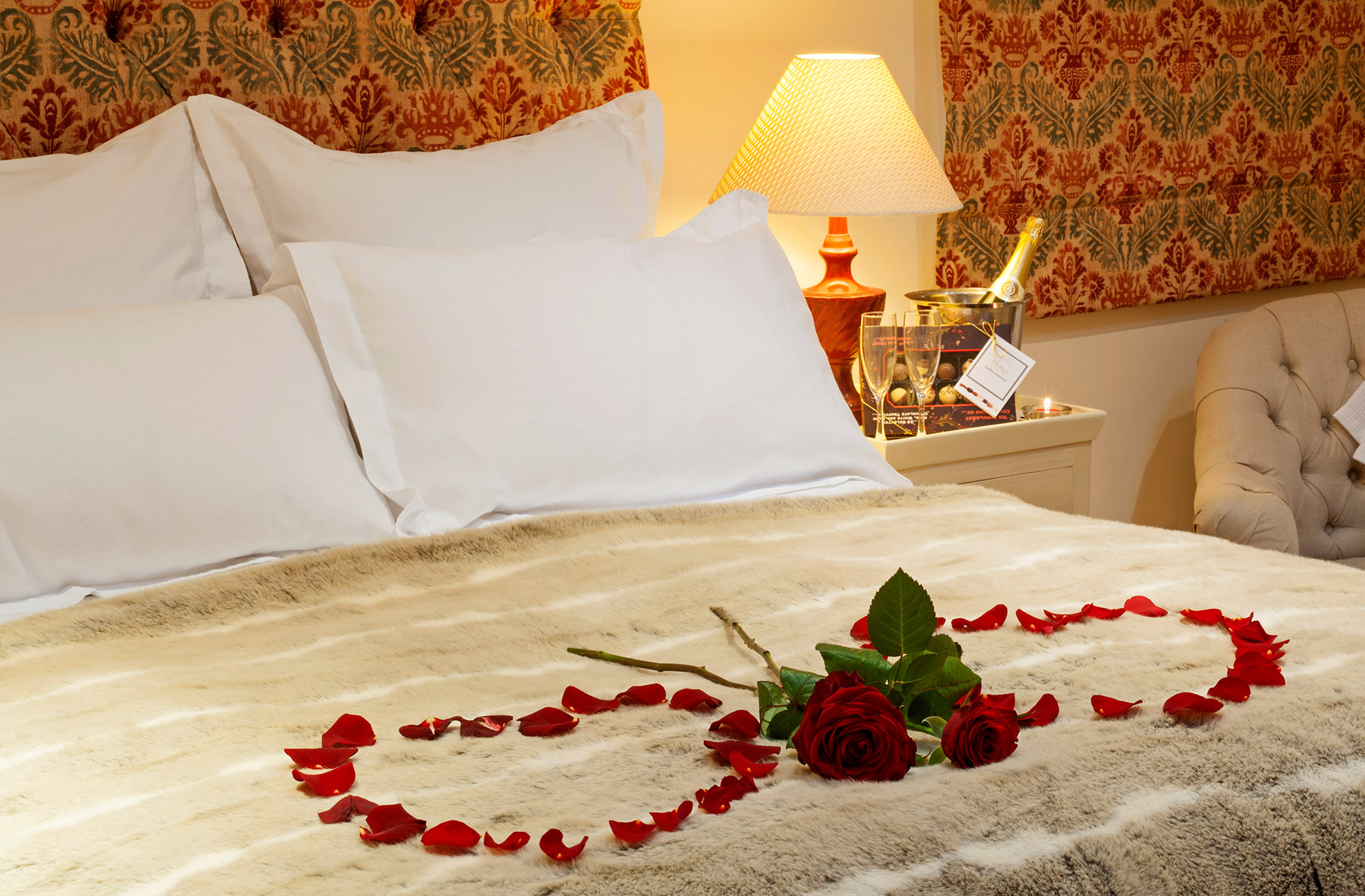 The bed in the Stone Lodge bridal suite at Combermere Abbey is scattered with rose petals