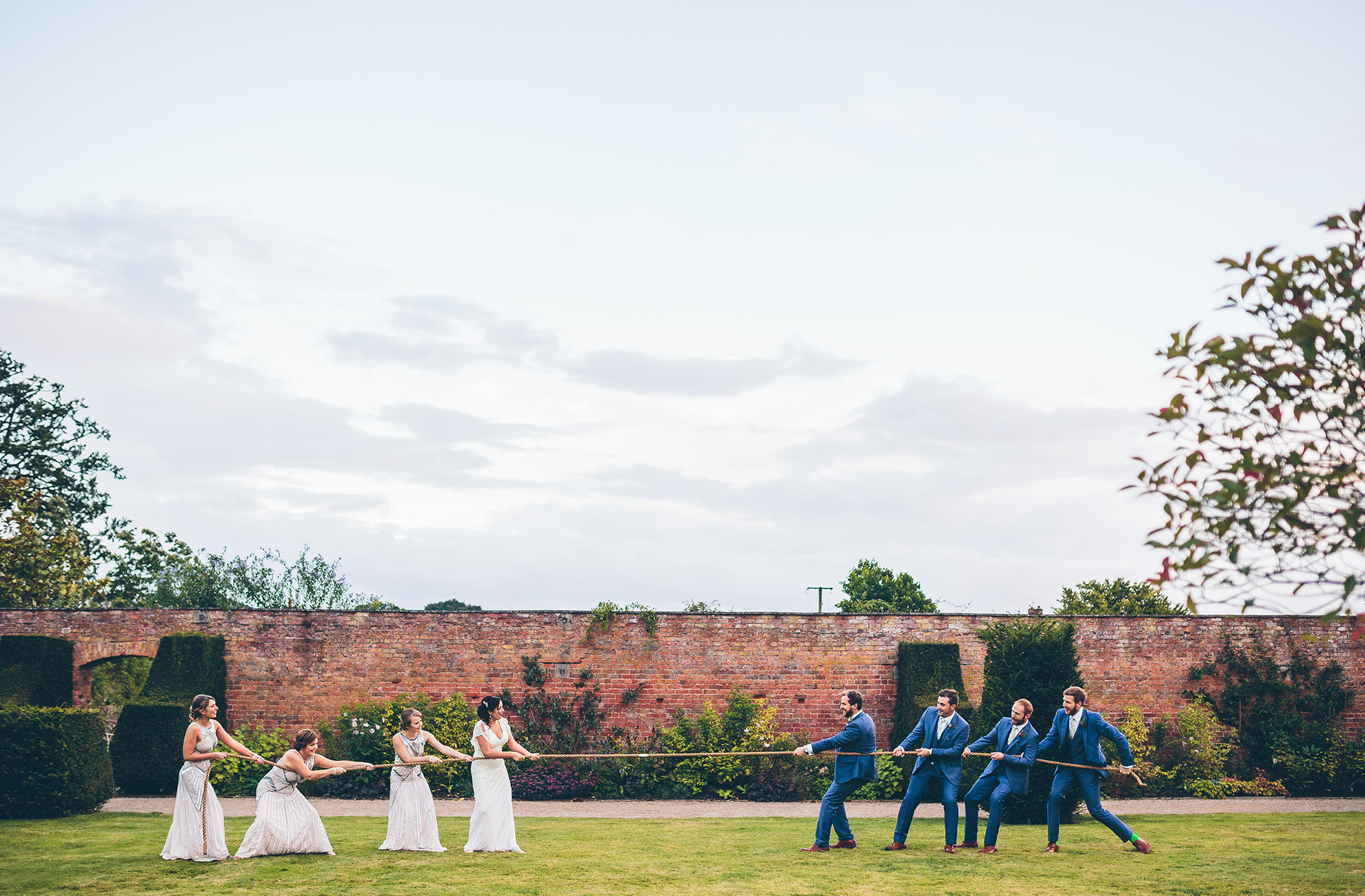 The wedding party play a game of tug of war in the walled gardens at Combermere Abbey wedding venue in Cheshire