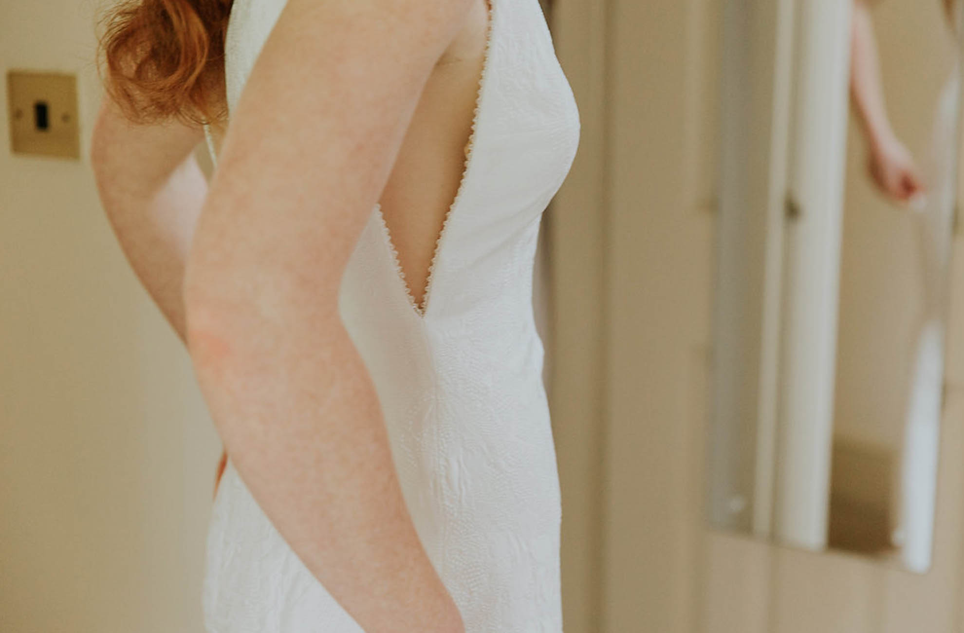 The bride wore a form fitting dress with cut out side details for her wedding at Combermere Abbey