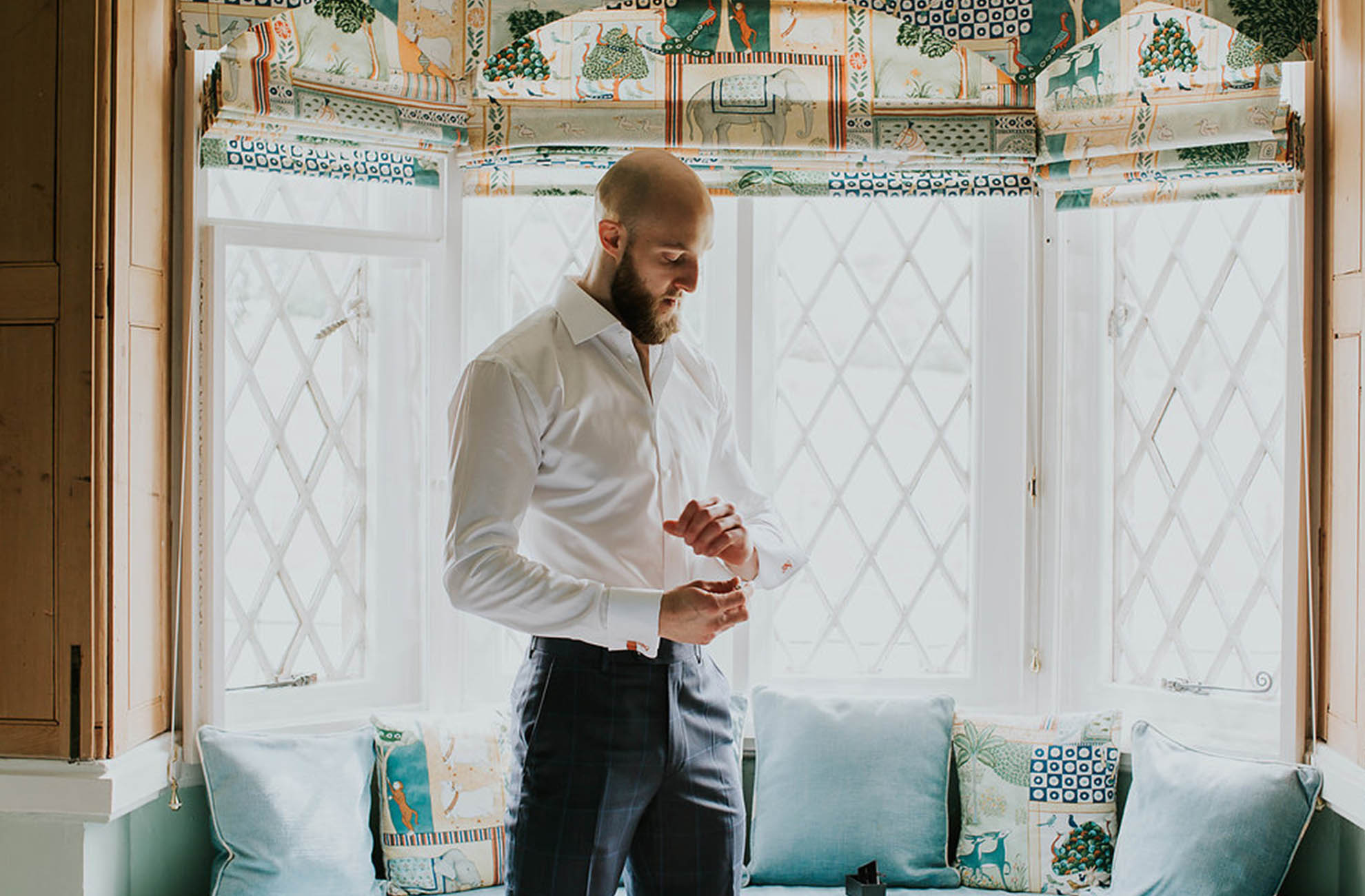 The groom prepares for his wedding ceremony in one of the cottages at Combermere Abbey