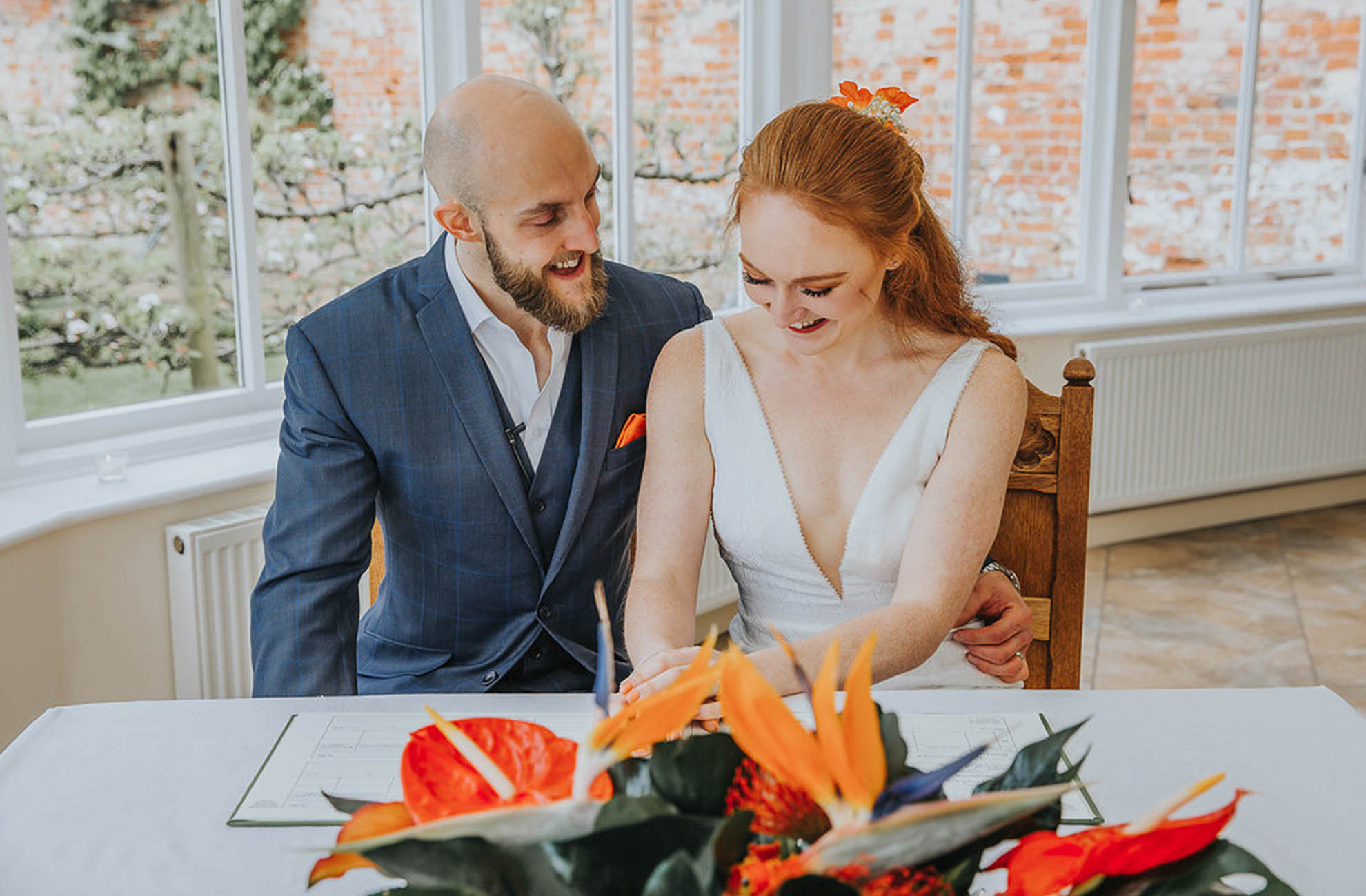 The newlyweds sign the wedding register in the Glasshouse at Combermere Abbey