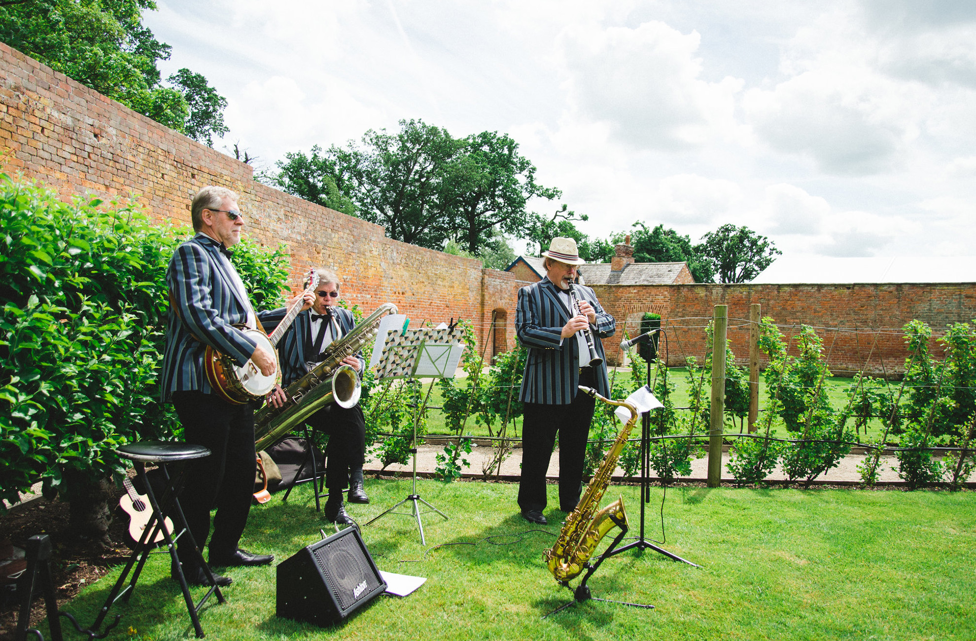 A wedding band play in the fruit tree maze during an outdoor drinks wedding reception at Combermere Abbey