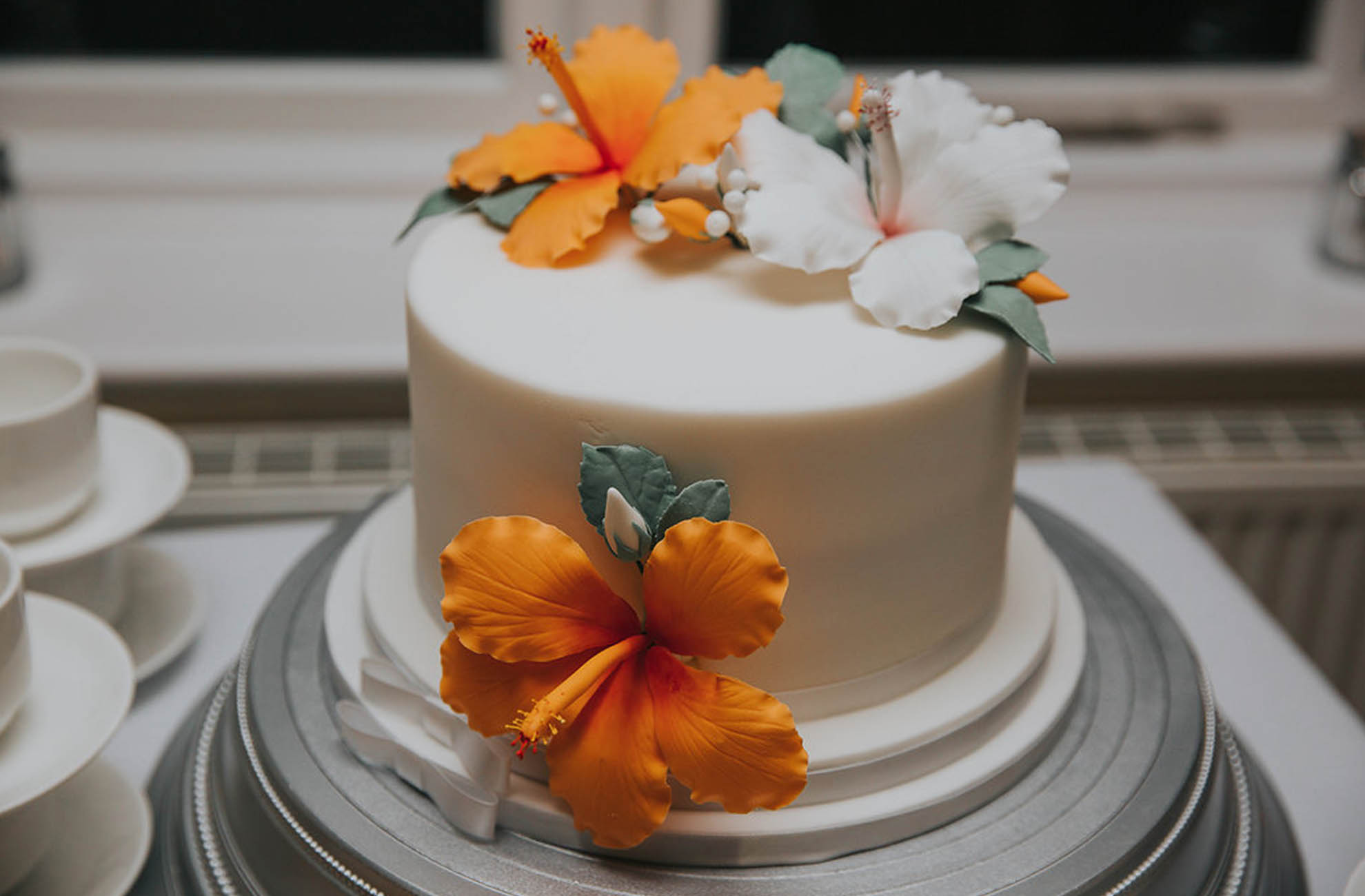 Tropical orange flowers adorn a traditional white wedding cake for an intimate wedding at Combermere Abbey