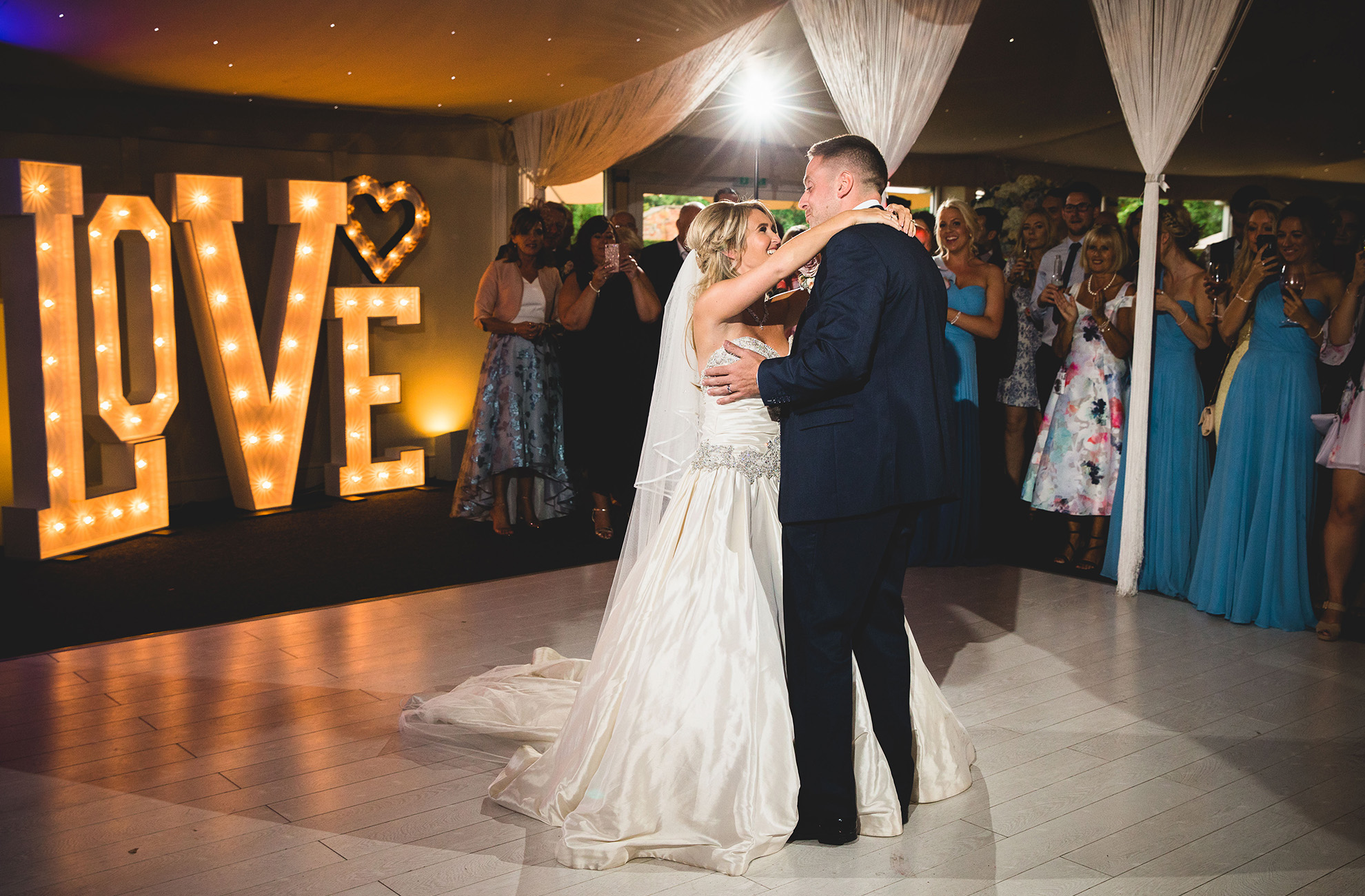 A couple dance in front of giant love letters during their wedding reception at Combermere Abbey