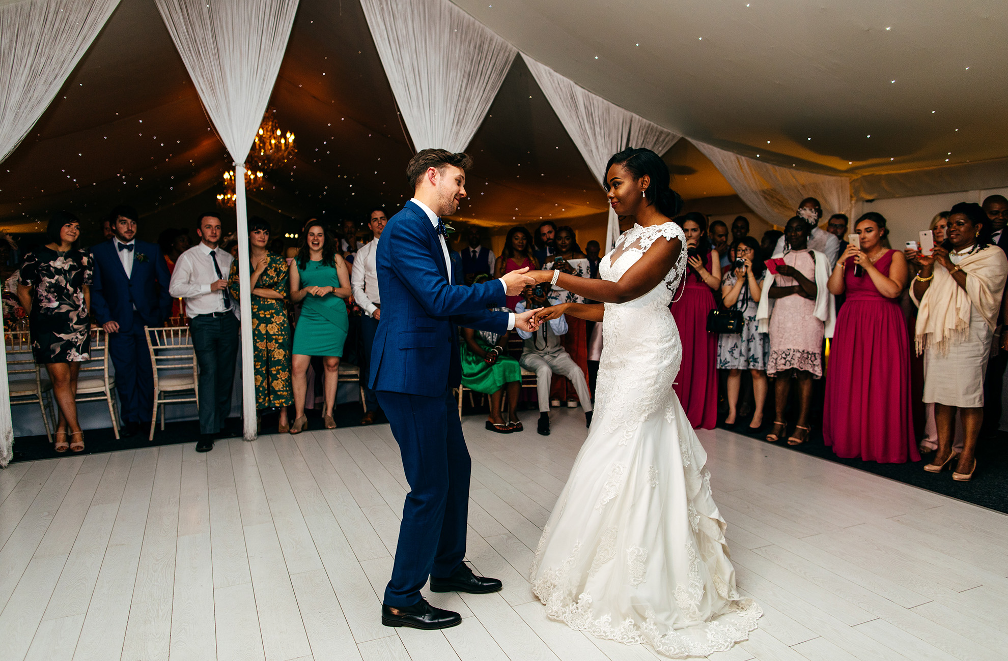 Newlyweds are surrounded by guests as they perform their first dance during their reception at Combermere Abbey