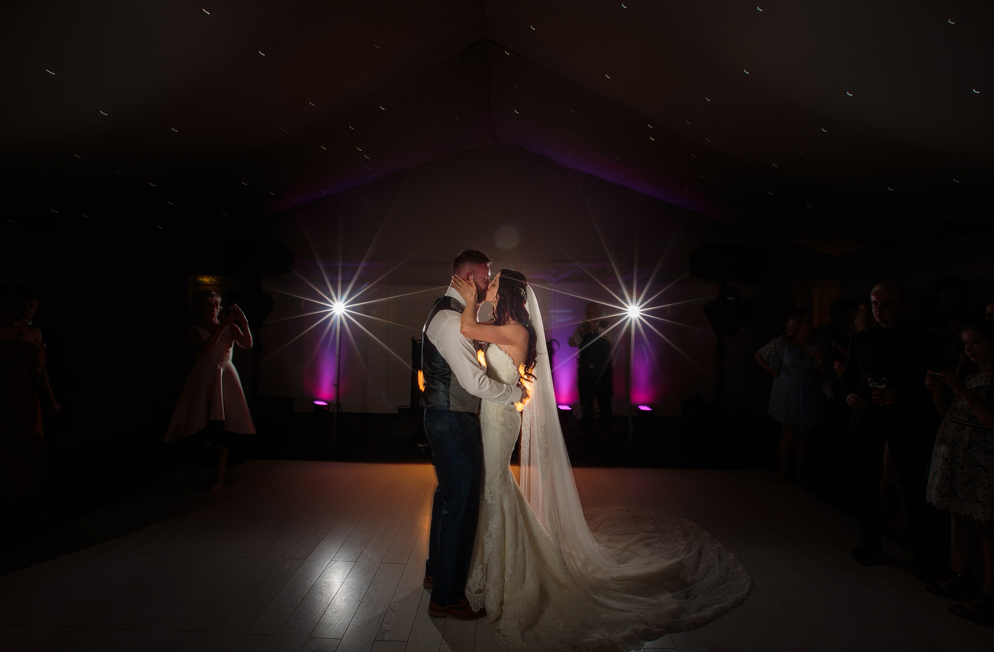 Newlyweds share a kiss during their first dance at Combermere Abbey