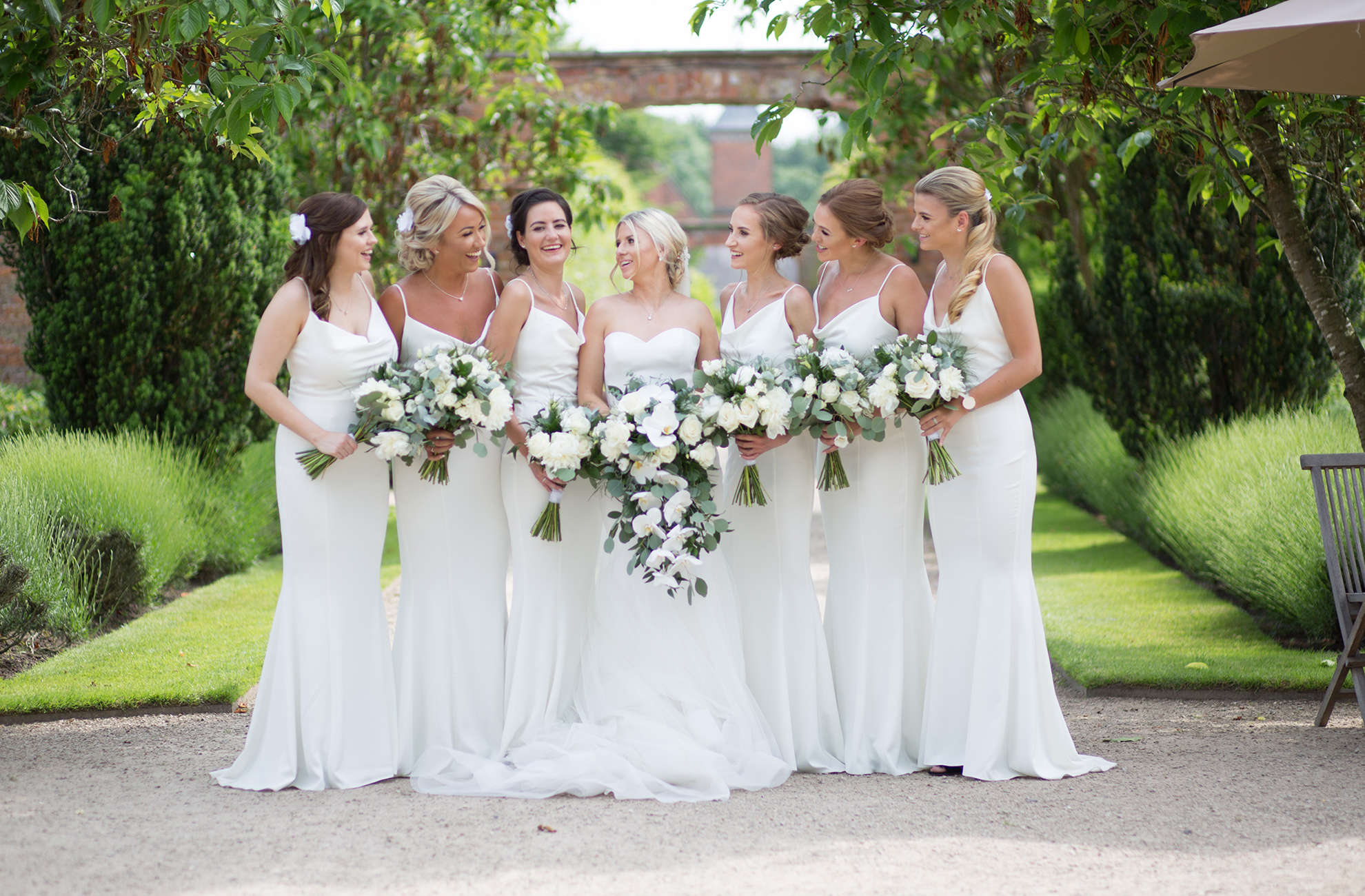 Bridesmaids hold white rose wedding bouquets in the gardens at Combermere Abbey
