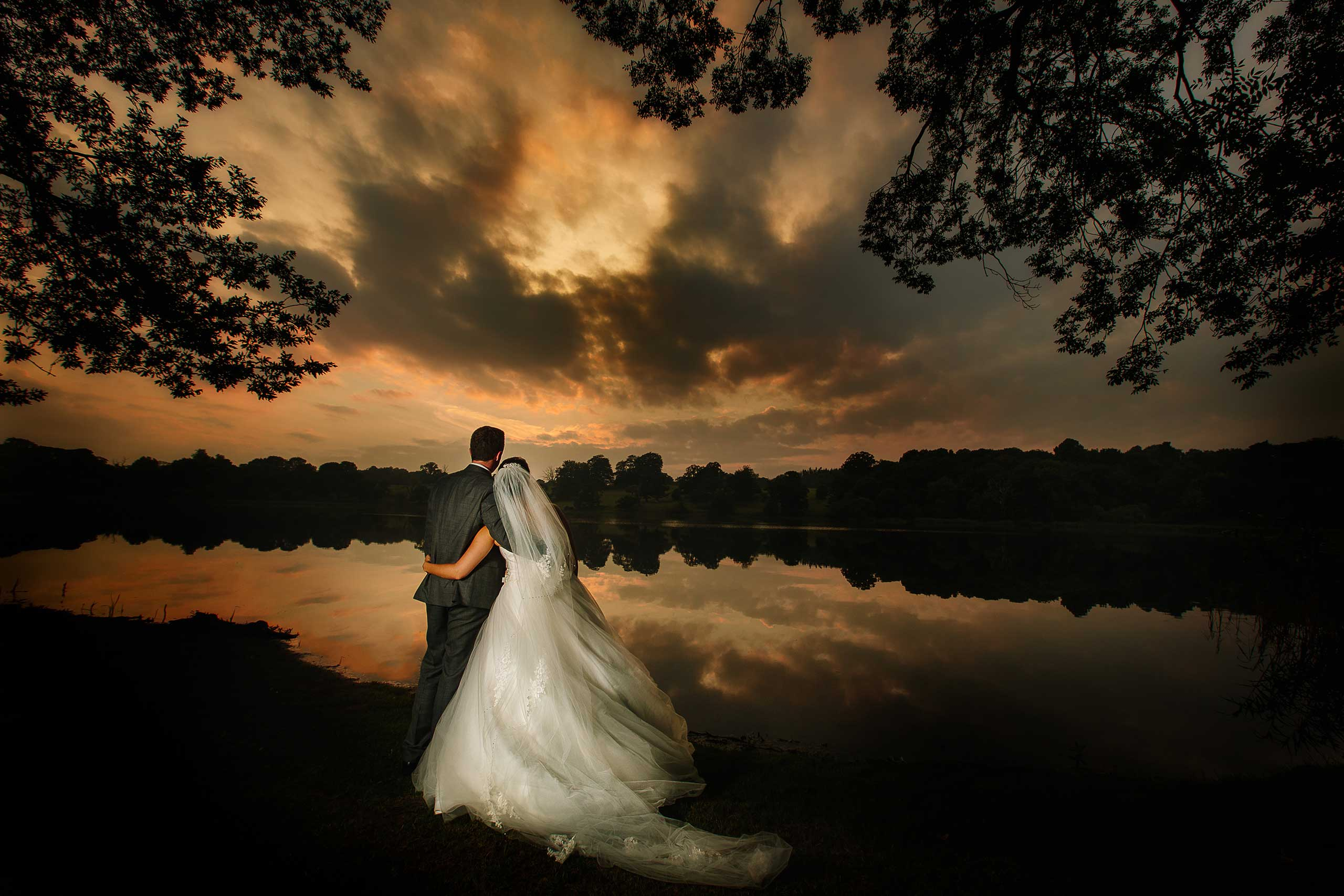 Golden hour wedding photograph at Combermere Abbey by the lakeside